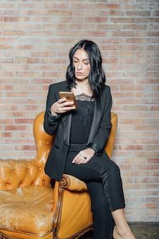 Jonge mooie vrouw die binnen het gebruiken van slimme telefoon stelt