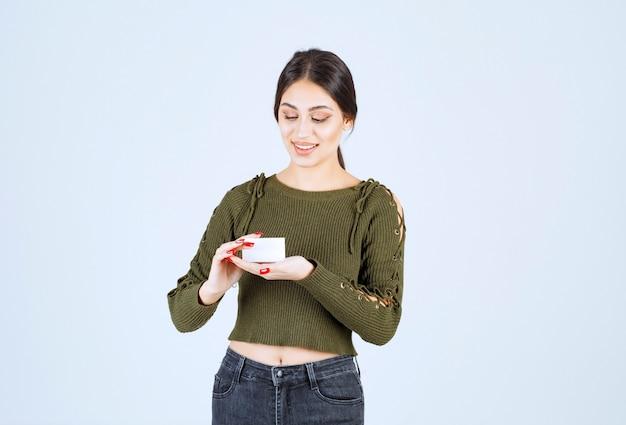 Jonge mooie vrouw die blanco visitekaartje op witte achtergrond bekijkt.