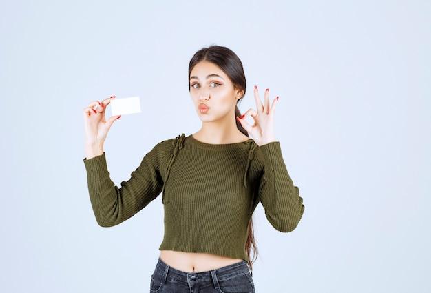 Jonge mooie vrouw die blanco visitekaartje toont en ok teken geeft.