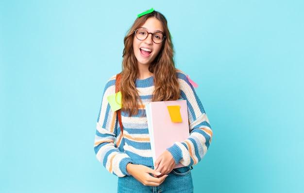 Jonge mooie vrouw die blij en aangenaam verrast kijkt met een tas en boeken vasthoudt