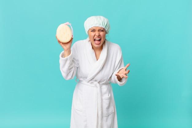 Jonge mooie vrouw die boos, geïrriteerd en gefrustreerd kijkt en een badjas draagt na het douchen