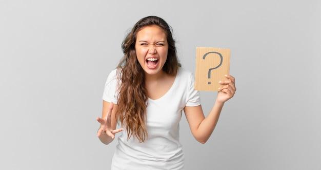 Jonge mooie vrouw die boos, geïrriteerd en gefrustreerd kijkt en een vraagteken vasthoudt