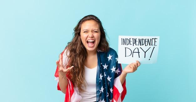 Jonge mooie vrouw die boos, geïrriteerd en gefrustreerd kijkt naar het concept van de onafhankelijkheidsdag