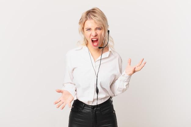 Jonge mooie vrouw die boos, geïrriteerd en gefrustreerd kijkt. telemarketing concept