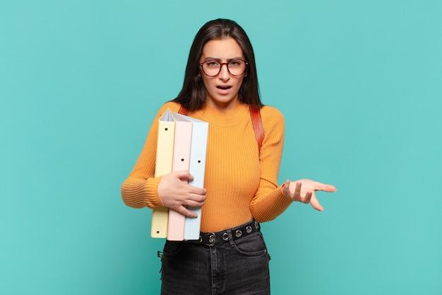 Jonge mooie vrouw die boos, geïrriteerd en gefrustreerd schreeuwt wtf of wat is er mis met je. studentenconcept Premium Foto