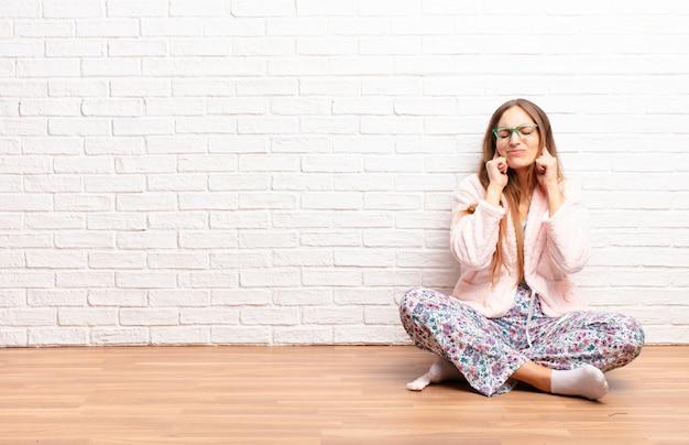 Jonge mooie vrouw die boos, gestrest en geërgerd kijkt, beide oren bedekkend met een oorverdovend geluid, geluid of luide muziek. thuis concept