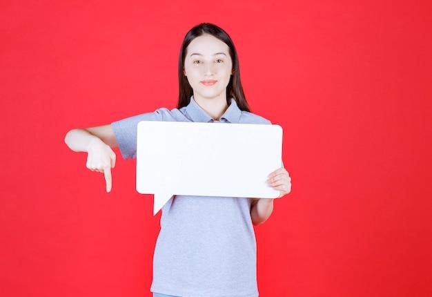 Jonge mooie vrouw die bord vasthoudt en met de vinger naar beneden wijst