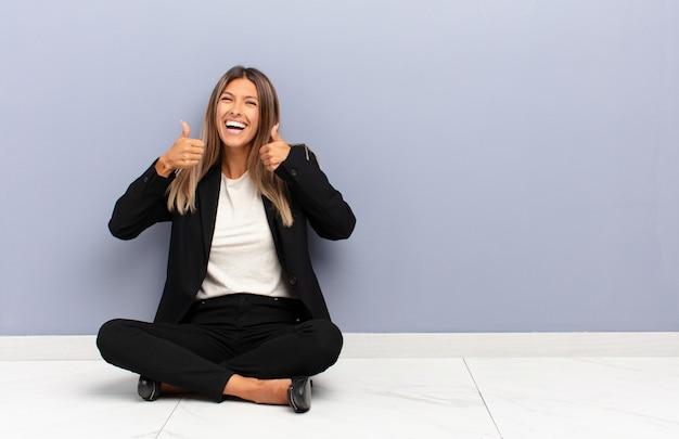 Jonge mooie vrouw die breed kijkt gelukkig, positief, zelfverzekerd en succesvol, met beide duimen omhoog bedrijfsconcept