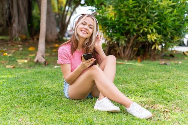Jonge mooie vrouw die buitenshuis muziek luistert met de mobiel