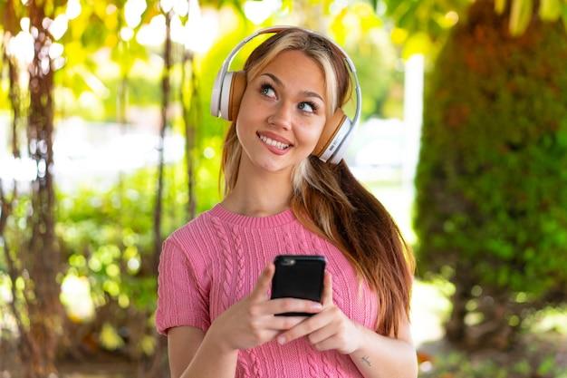Jonge mooie vrouw die buitenshuis muziek luistert met een mobiel en denkt