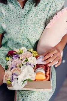 Jonge mooie vrouw die cake in moderne keuken eet. huiskleding.