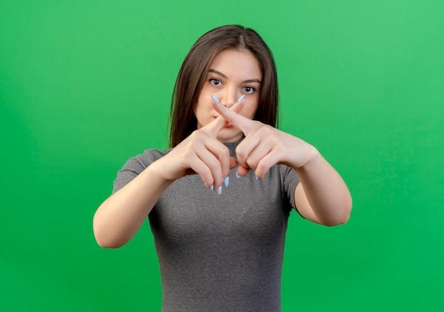 Jonge mooie vrouw die camera bekijkt en geen gebaar doet dat op groene achtergrond wordt geïsoleerd