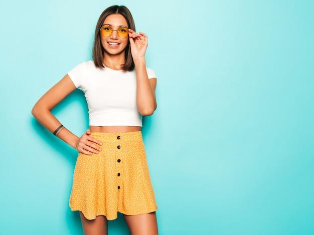 Jonge mooie vrouw die camera bekijkt. trendy meisje in casual zomer wit t-shirt en gele rok in ronde zonnebril. positieve vrouw toont gezichtsemoties. grappig model dat op blauw wordt geïsoleerd