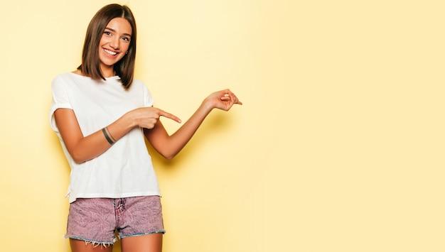 Jonge mooie vrouw die camera bekijkt. trendy meisje in casual zomer wit t-shirt en jeans short. positieve vrouw toont gezichtsemoties. model wijst met haar vingers in één richting