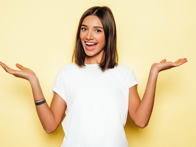 Jonge mooie vrouw die camera bekijkt. trendy meisje in casual zomer wit t-shirt. positieve vrouw toont gezichtsemoties. model met iets op beide platte handen voor een vergelijkbare productkeuze