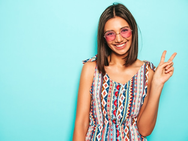 Jonge mooie vrouw die camera bekijkt. trendy meisje in casual zomerjurk en ronde zonnebril. positieve vrouw toont gezichtsemoties. grappig model dat op blauw wordt geïsoleerd