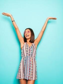 Jonge mooie vrouw die camera bekijkt. trendy meisje in casual zomerjurk en ronde zonnebril. positieve vrouw toont gezichtsemoties. model die haar handen opheft en viert
