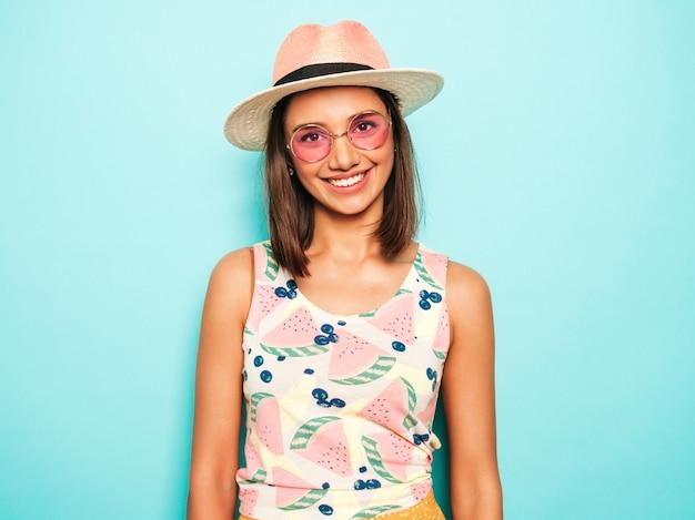 Jonge mooie vrouw die camera in hoed bekijkt. trendy meisje in casual zomer wit t-shirt en gele rok in ronde zonnebril. positieve vrouw toont gezichtsemoties. grappig model dat op blauw wordt geïsoleerd