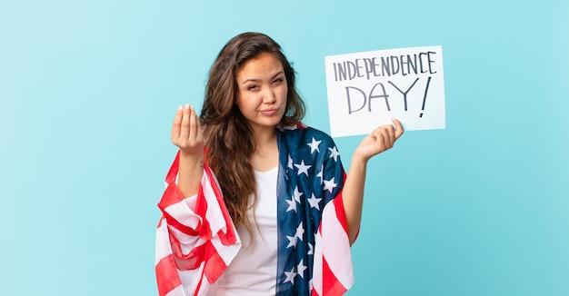 Jonge mooie vrouw die capice of geldgebaar maakt en je vertelt om het concept van de onafhankelijkheidsdag te betalen