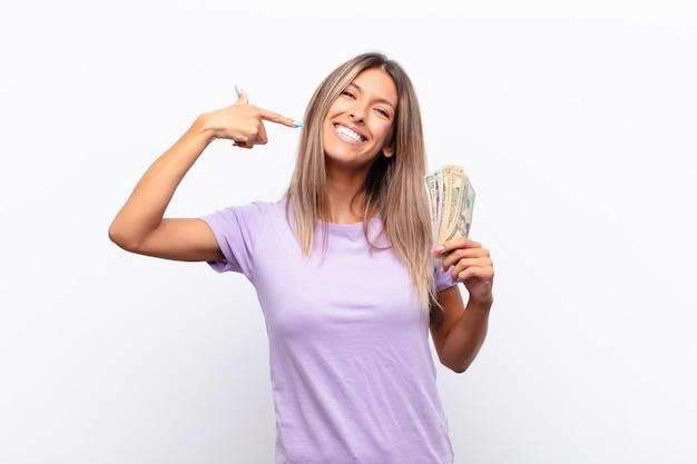 Jonge mooie vrouw die capice of geldgebaar maakt en je zegt dat je je schulden moet betalen! met bankbiljetten