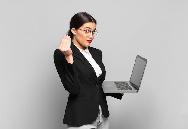 Jonge mooie vrouw die capice of geldgebaar maakt en u vertelt om uw schulden te betalen!. laptopconcept