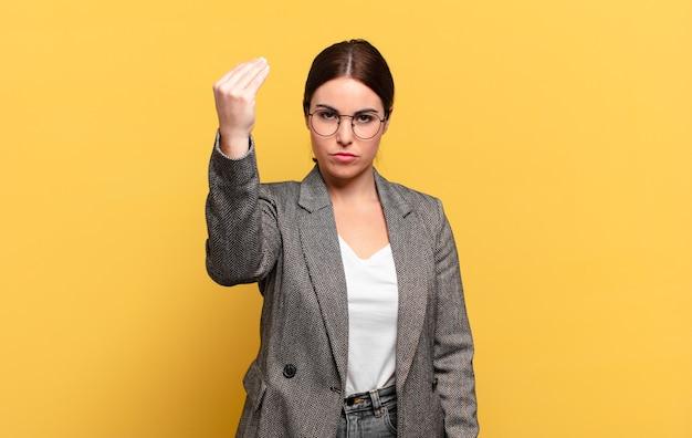 Jonge mooie vrouw die capice of geldgebaar maakt en u vertelt om uw schulden te betalen!