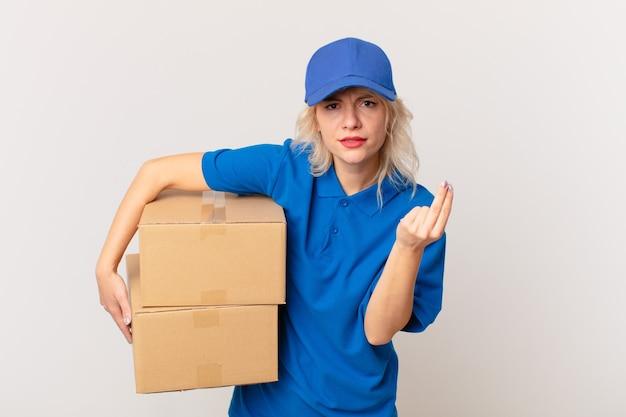 Jonge mooie vrouw die capice of geldgebaar maakt en u vertelt te betalen. pakket leveren concept