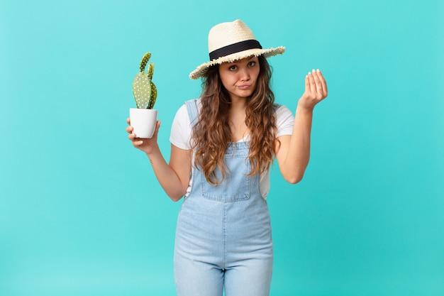 Jonge mooie vrouw die capice of geldgebaar maakt, zegt dat je moet betalen en een cactus vasthoudt