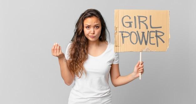 Jonge mooie vrouw die capice of geldgebaar maakt, zegt dat je moet betalen en een girlpower-banner vasthoudt