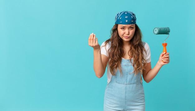 Jonge mooie vrouw die capice of geldgebaar maakt, zegt dat je moet betalen en een muur moet schilderen