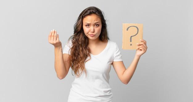 Jonge mooie vrouw die capice of geldgebaar maakt, zegt dat je moet betalen en een vraagteken vasthoudt