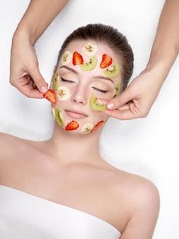 Jonge mooie vrouw die cosmetisch fruit gezichtsmasker van aardbei, banaan en kiwi krijgt bij schoonheidssalon