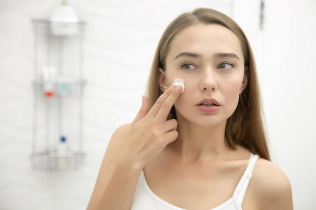 Jonge mooie vrouw die crème aan het gezicht in de badkamer toepast