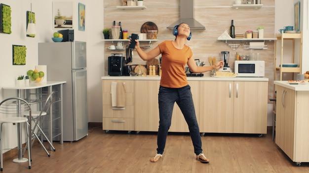 Jonge mooie vrouw die danst terwijl ze naar muziek luistert in blauwe draadloze koptelefoons in de keuken. energieke, positieve, vrolijke, grappige en schattige huisvrouw die alleen in huis danst. entertainment en ontspanning
