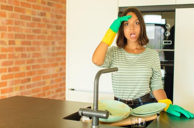 Jonge mooie vrouw die de afwas doet en er blij, verbaasd en verrast uitziet, glimlachend en zich verbluffend en ongelooflijk goed nieuws realiseert
