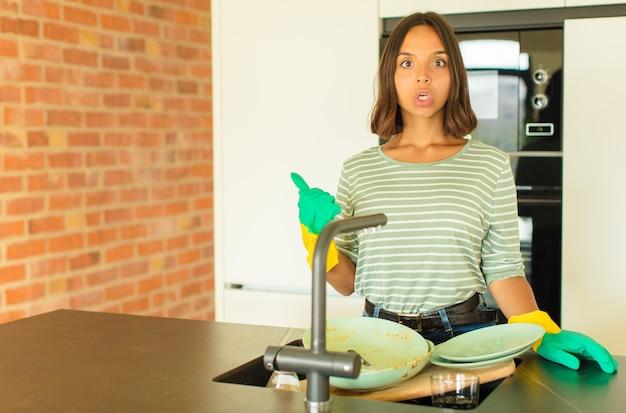 Jonge, mooie vrouw die de afwas doet, kijkt verbaasd van ongeloof, wijst naar een voorwerp aan de zijkant en zegt wauw, ongelooflijk
