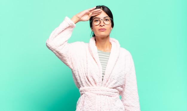 Jonge mooie vrouw die de camera begroet met een militaire groet in een daad van eer en patriottisme en respect toont. pyjama's concept