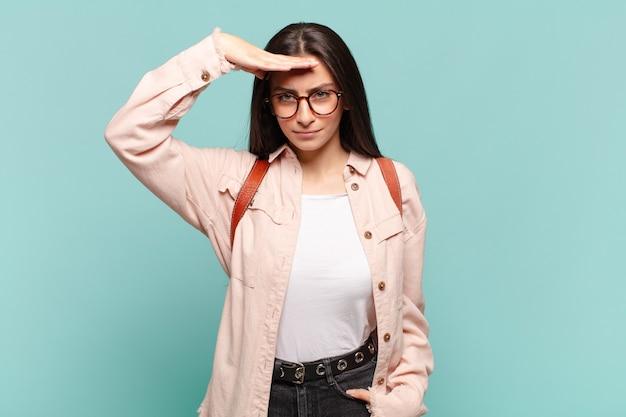 Jonge mooie vrouw die de camera begroet met een militaire groet in een daad van eer en patriottisme, respect tonen