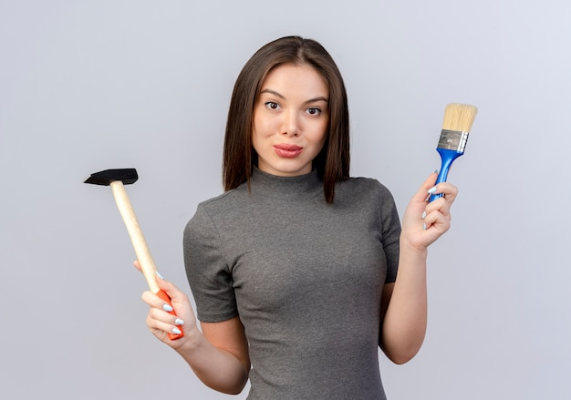 Jonge mooie vrouw die de hamer en de verfborstel van de cameraholding bekijkt die op witte achtergrond wordt geïsoleerd