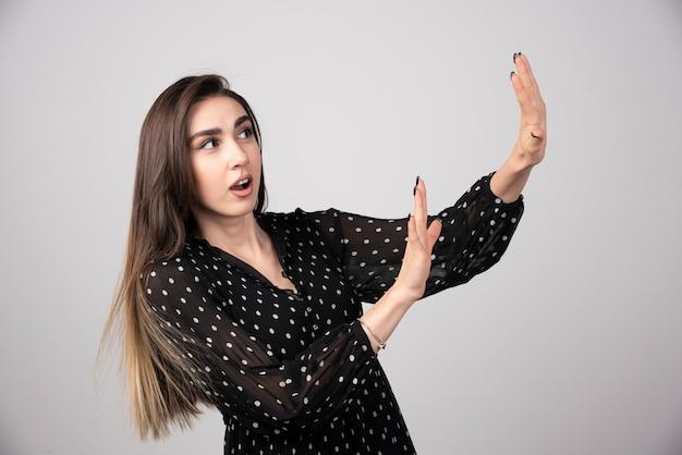 Jonge mooie vrouw die de handpalmen wegtrekt die weigering en ontkenning tonen.