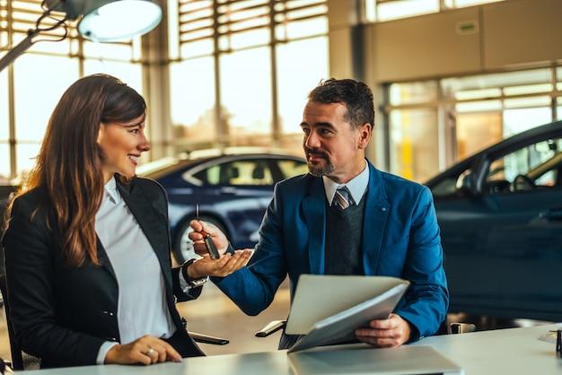 Jonge mooie vrouw die de sleutels van haar nieuwe auto ontvangt.