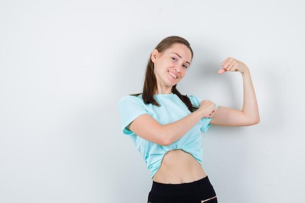 Jonge mooie vrouw die de spieren van de arm toont, met de hand op de arm in een t-shirt en er trots uitziet, vooraanzicht.