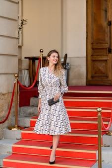 Jonge mooie vrouw die de stappen op het rode tapijt loopt