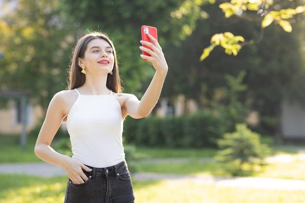 Jonge mooie vrouw die de telefoon in het park met behulp van