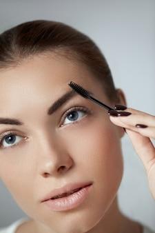 Jonge mooie vrouw die de vorm van wenkbrauwen corrigeert. contouring wenkbrauw make-up.