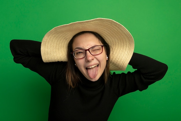 Jonge mooie vrouw die de zomerhoed in een zwarte coltrui en een bril draagt die aan voorzijde tong blij en positief kijkt die zich over groene muur bevindt