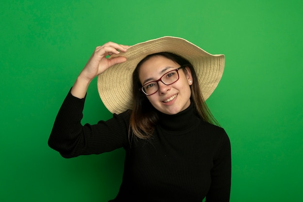 Jonge mooie vrouw die de zomerhoed in een zwarte coltrui en een bril draagt die voorzijde gelukkig en positief status over groene muur bekijkt