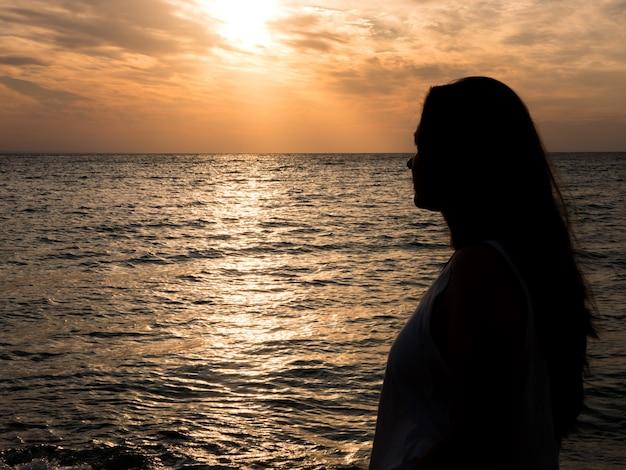 Jonge mooie vrouw die de zonsondergang aan zee bewondert. mooie vrouw herenigd met de natuur