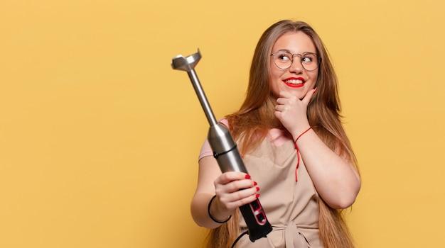 Jonge mooie vrouw die denkt of twijfelt aan het concept van de bakkersblender van de uitdrukking Premium Foto
