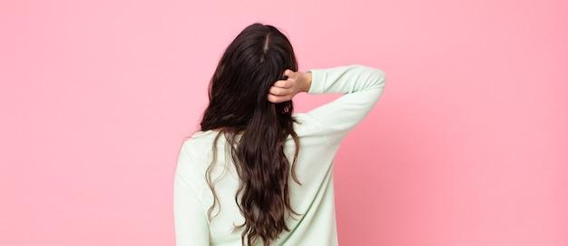 Jonge mooie vrouw die denkt of twijfelt, hoofd krabt, zich verward en verward voelt, achter- of achteraanzicht